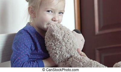 A cute little girl is hugging a gray teddy