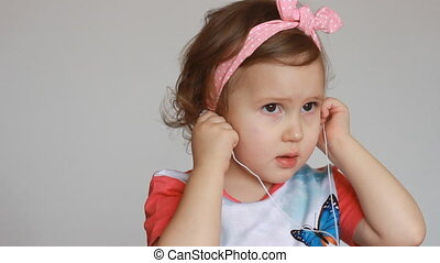A cute little girl is listening to music on headphones. Funny child with a player in the ears. The concept of music and songs.