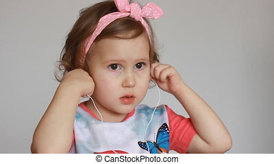 A cute little girl is listening to music on headphones....