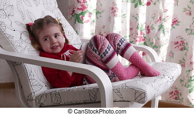 A cute little girl is sitting in armchair near the window playing with digital tablet