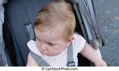 A cute little girl is surprised. The child is sitting in a...