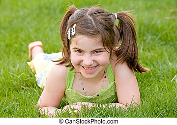 Little Girl Laying in the Grass Laughing