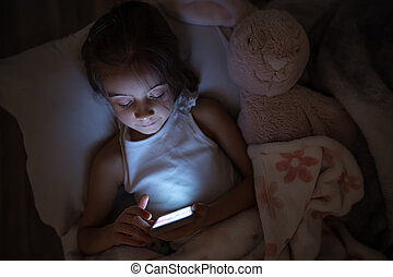 A cute little girl lies on a pillow and enthusiastically plays on the phone at night in bed instead of sleeping top view.