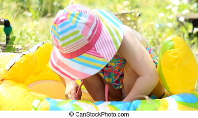 A cute little girl Playing a swimsuit on the beach in a hot summer.