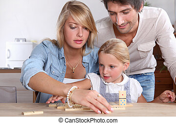 A cute little girl playing dominos with her parents.