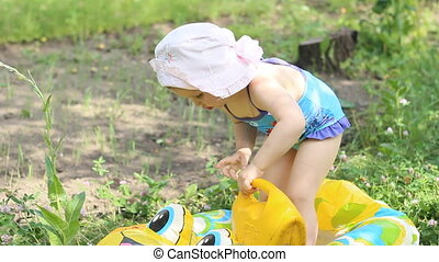 little girl Playing with water and watering can in a swimsuit on the beach