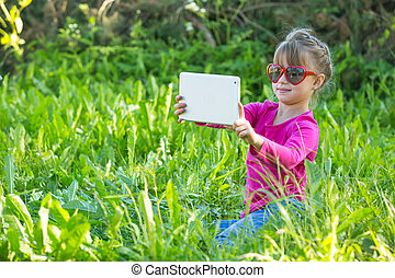 A cute little girl while taking a selfie (self portrait) at tablet PC in the park.