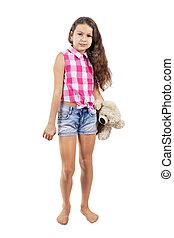 A cute little girl with a teddy bear in a sleeveless shirt