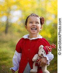 A cute little happy girl holding a teddy bear in the  on a sunny autumn day