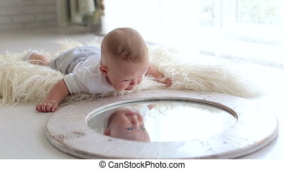 A cute little newborn baby is playing with a mirror at home lying on the bed.