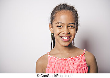 Cute nine years old child with pink dress on studio white...