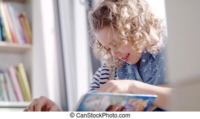 A cute small girl with mother indoors at home, reading book.