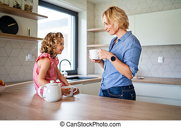 A cute small girl with mother indoors in kitchen at home.