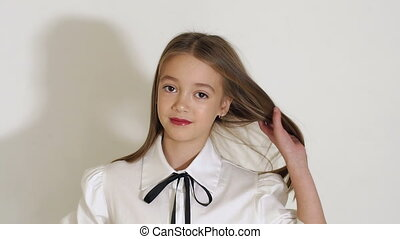 A cute teen girl in a white blouse posing in the Studio on a white background.