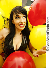 a cute woman surrounded by colorful balloons. - A stock...