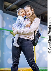 A cute young Caucasian mother holds a baby daughter in her arms, looks at the camera and smiles happily and laughs. vertical photo, close-up, soft focus, blur background