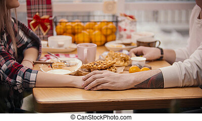 A cute young couple holding hands in the cafe