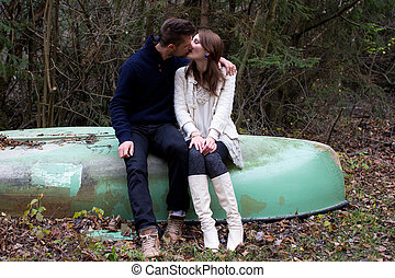 A cute young couple sitting on a old boat