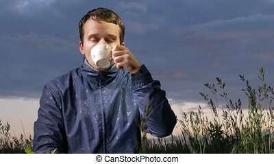 A cute young man drinks a hot drink at sunset on the field. Beautiful sky on a background.
