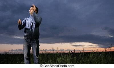 A cute young man waves off mosquitoes at sunset on the field. Beautiful sky on a background.