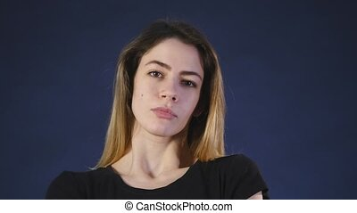 A cute young white woman looks into the camera on a black background