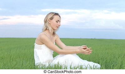 A cute young woman sits in the grass in an open field and looks at the camera