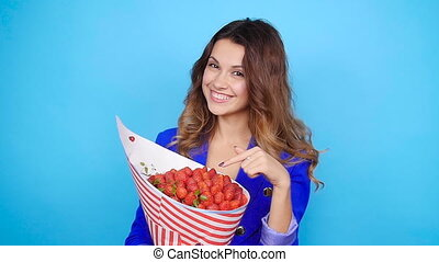 A cute young woman with a bouquet of strawberries