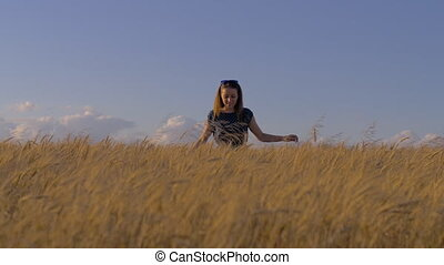 A cute younger girl walks through a golden yellow wheat...