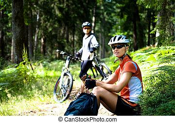 cycling woman - A cycling woman taking a break