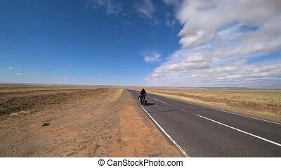 A cyclist rides on an asphalt road in the steppes of Mongolia.