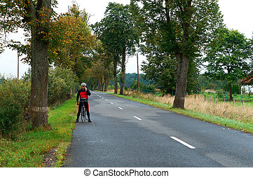 a cyclist talking on the phone on the road, Bicycle travel