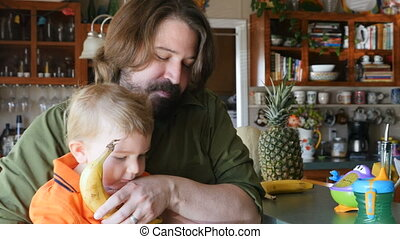A dad peels a banana snack and gives some to his toddler son