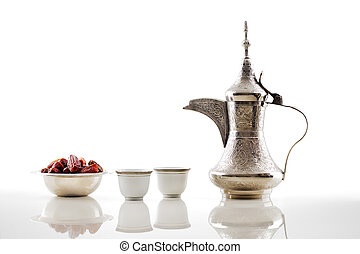 A dallah is a metal pot with a long spout designed specifically for making Arabic coffee, seen here with a bowl of dried dates and two cups