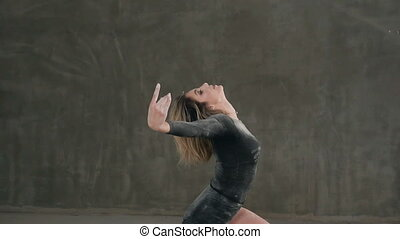 A dancer dressed in black body suit perform a modern dance...