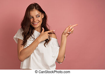 A dark-haired girl in a white top is standing on a pink background, pointing fingers to the throne and smiling.