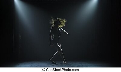 A dark silhouette of an attractive dancer is emotionally ...
