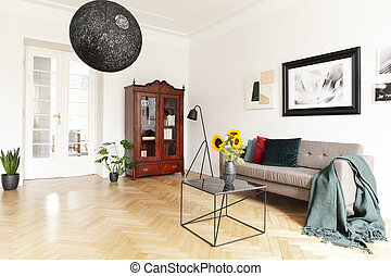 A dark, wooden, display cabinet by a white wall of an eclectic living room interior with yellow sunflowers and art