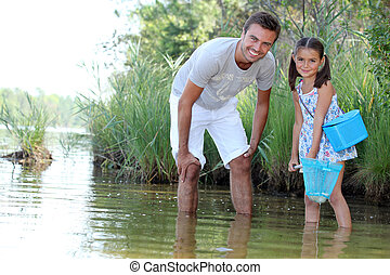 a daughter and her father fishing in a river