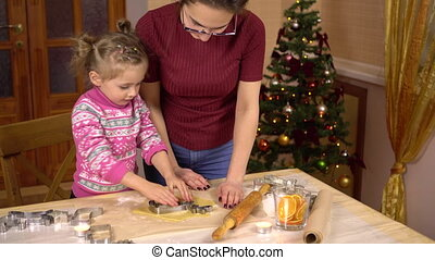 A daughter with a young mother makes a traditional festive Christmas cookies in the form of a deer. A figurine is placed in the dough. 4k