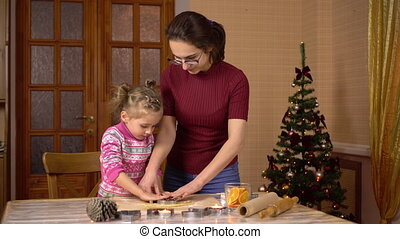 A daughter with a young mother makes gingerbread Christmas cookies. A figurine is placed in the dough. 4k