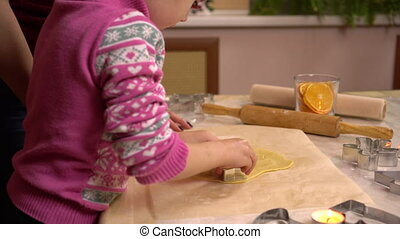 A daughter with a young mother makes gingerbread Christmas cookies in the form of stars. A figurine is placed in the dough. 4k