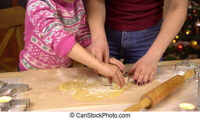 A daughter with a young mother makes the traditional festive Christmas cookies in the form of human. A figurine is placed in the dough. 4k