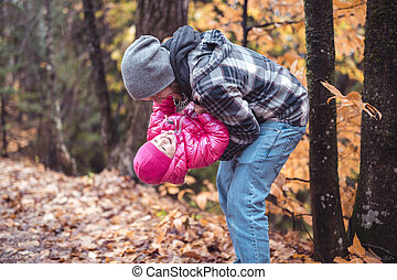 Daughter with dad walking in the autumn forest