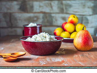 A deep plate with cottage cheese on the table of a country house. Ripe nectarines and pear, wooden spoons.