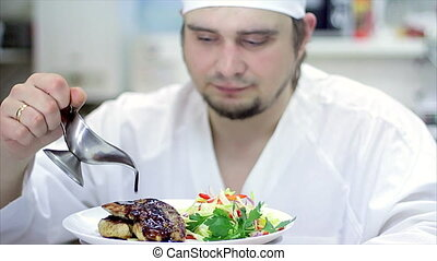 A delicious gourmet meal is being given the finishing touches by the chef in a restaurant or hotel kitchen, ready for service to the customer. Slow motion