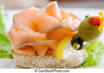 A delicious smoked salmon canape with lemon, cucumber and olive