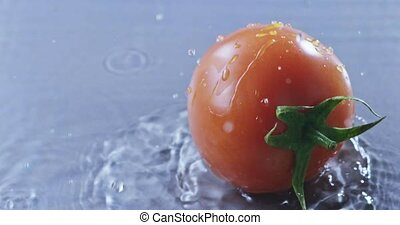 A delicious tomato with a green tail fell to the surface...