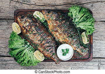 A deliciously roasted carp on a grill, presented on a wooden board, and along the leaves of green salad and pieces of lemon