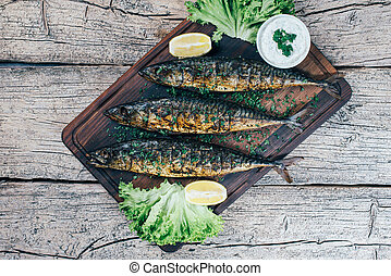 A deliciously roasted mackerel on a grill, presented on a wooden board, and along the leaves of green salad and pieces of lemon
