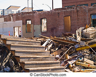 A demolition site with a pile of demolished brick wall and concrete debris